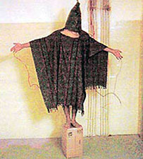 Human on box with electrodes attached to genitals ++ We Don't Torture - George Bush