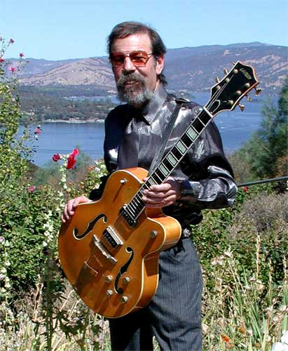 Mike Wilhelm holding Gretsch guitar, Clear Lake in background