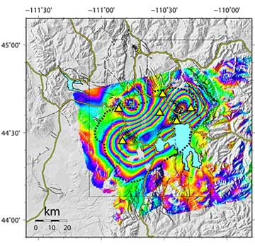 This interferogram provides a map view of ground movements at Yellowstone. Each color contour represents a line of equal uplift relative to the ENVISAT  satellite between Sept. 2004 and Aug. 2006. The center of the uplift is an elliptical region stretching from the northeastern part of the Yellowstone Caldera (the dashed black line) to the southwest. This area of maximum uplift encompasses both Yellowstone's resurgent domes, features long known for similar movements. During this time period, the north-rim uplift anomaly subsided (bullseye in the upper left part of the interferogram). The yellow lines are roads. The yellow triangles are locations of GPS stations with continuous data. The light blue lake within the caldera is Yellowstone Lake. Thin black lines are mapped faults. Figure courtesy of C. Wicks, USGS.
